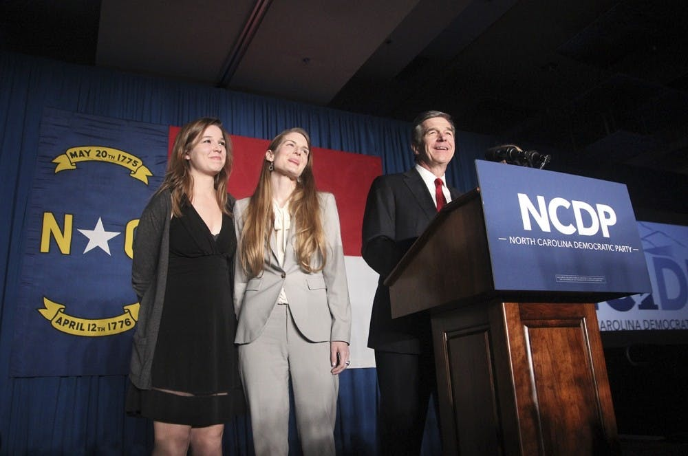 <p>North Carolina Governor-elect Roy Cooper and two of his daughters at the North Carolina Democratic Party</p>
