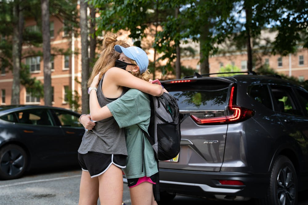 <p>First-year roommates Jenna Barnes (left) and Ainsley Kaplan (right) hug in the Hinton James parking lot on Tuesday, Aug. 18, 2020 following UNC's announcement that all classes will be moving to an online format.</p>