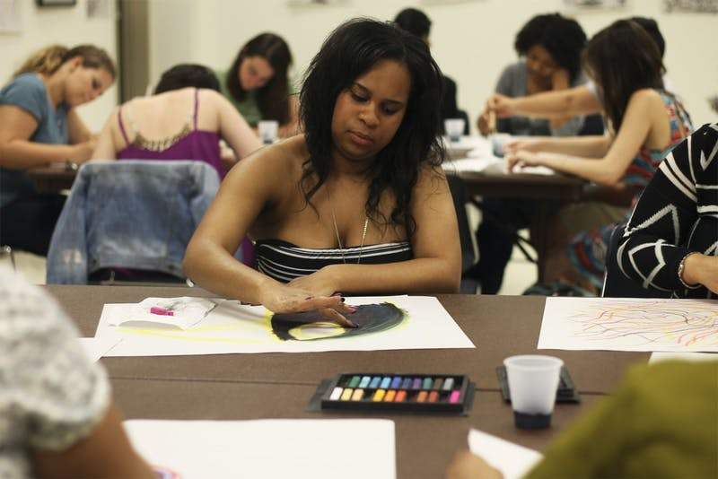 Global studies major Daleah Wilkerson paints at Healing Arts Night, hosted by Rethink: Psychiatric Illness in the Student Union on Tuesday.