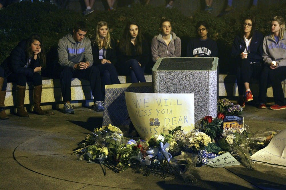 <p>Mourners gather at 8 p.m. Sunday with candles, flowers and notes to place in front of the Dean E. Smith Center. Students sang the alma mater after a moment of silence. Smith died Saturday night.</p>