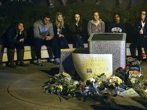 Mourners gather at 8 p.m. Sunday with candles, flowers and notes to place in front of the Dean E. Smith Center. Students sang the alma mater after a moment of silence. Smith died Saturday night.
