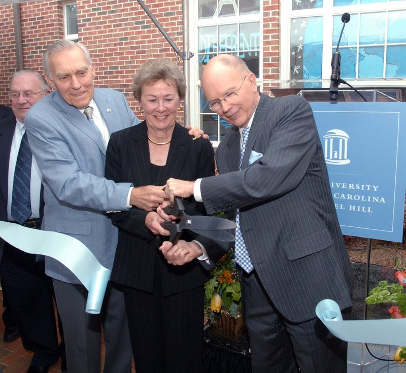 Former Chancellor Paul Hardin, left, and his wife Barbara, center, join UNC-Chapel Hill Chancellor James Moeser, right, cutting the ribbon at the dedication of Hardin Hall. Photo taken by Dan Sears and courtesy of UNC-Chapel Hill.