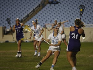 UNC sophomore defender Emma Trenchard (23) charges at High Point midfielder Kaely Kyle (31) in Kenan Memorial Stadium on Friday, Feb. 15, 2019. UNC won 13-9.