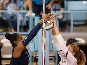 Junior middle blocker Skyy Howard (8) jumps to block the ball in the UNC Women's volleyball game against Virginia Tech at the Woolen Gymnasium on Oct. 10. The Heels won 3-0.