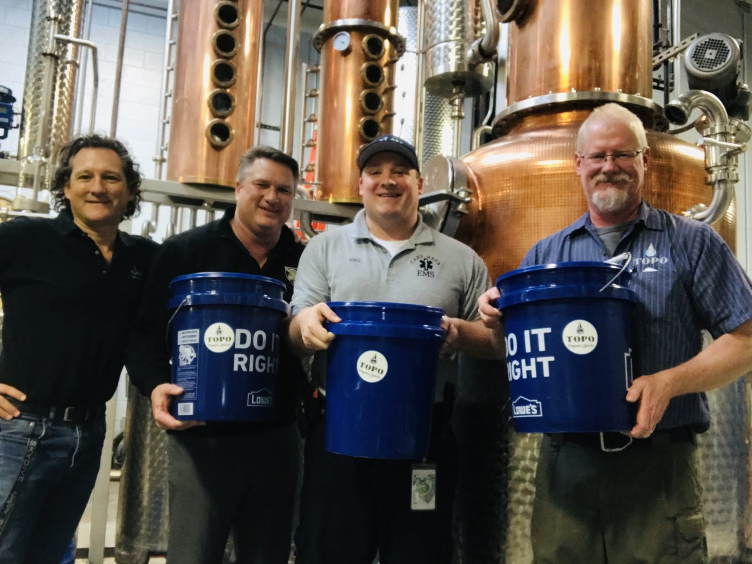 Top of The Hill Restaurant & Brewery is now producing hand sanitizer after the U.S. Food and Drug Administration gave distilleries the approval to do so because of COVID-19. (From left) TOPO Spirit Guide Esteban McMahan, TOPO Proprietor Scott Maitland, Axon & Wake EMS Evan MacIntyre and TOPO Head Distiller George Dusek pose for a picture in the TOPO distillery. Photo courtesy of Esteban McMahan.