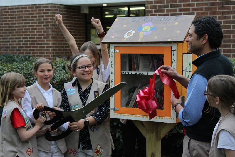 Girl Scout Troop 3064 and Mayor Mark Kleinschmidt officially install the Little Free Libraries with a ribbon-cutting ceremony at Community Center Park on Thursday evening.