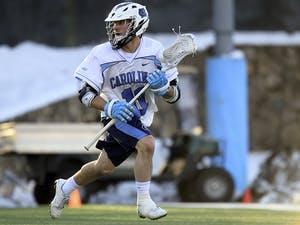 Senior attackman Joey Sankey (11) carries the ball down the field during the Feb. 27 12-10 win over the University of Denver.