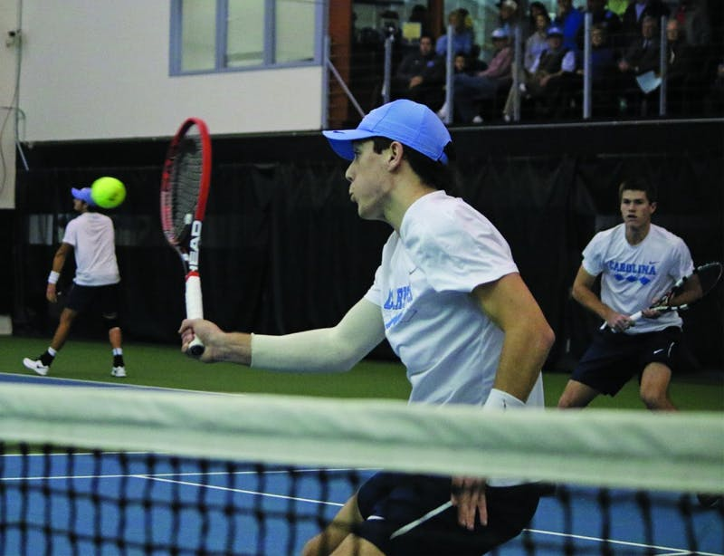 Sophomore Robert Kelly returns a ball while his doubles teammate Brett Clark looks on in No. 7 UNC Men's Tennis team's victory over No.5 Oklahoma 4-3 Sunday afternoon.