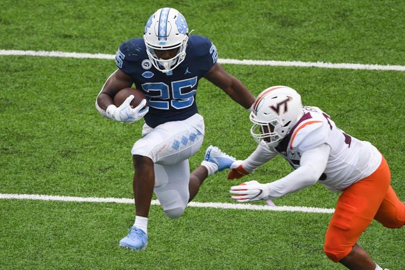 UNC junior running back Javonte Williams (25) attempts to pass Virginia Tech junior defensive back Jermain Waller (28) during a game in Kenan Memorial Stadium on Saturday, Oct. 10, 2020.