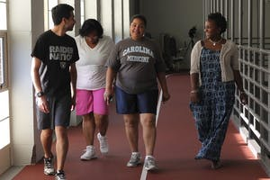 Milele Bynum, center, walks with participants of Walking in Faith, a program she started, at the indoor track of Lyon Park in Durham.