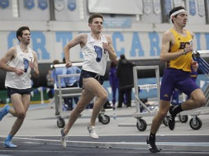 Jake McEneaney (center), a sophomore distance runner for UNC, tries to pull ahead of a runner from Eastern Carolina during the Men's One Mile Run in the Dick Taylor Carolina Cup at Eddie Smith Field House on Saturday, Jan. 12, 2019. McEneaney placed eighth in the event with a time of 4:27.67.
