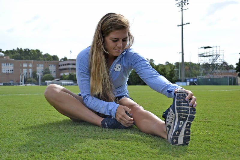 Women's soccer player Alexa Newfield stretches her repeatedly injured knee.