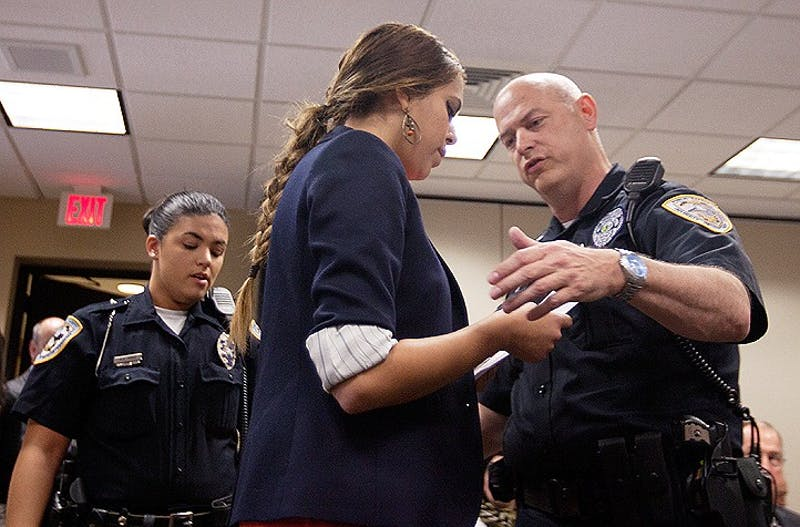 Zaina Alsous, a junior at UNC-Chapel Hill and member of Student Action with Workers, is escorted out of the Board of Governors meeting on Friday by police. Alsous interrupted the meeting to protest Senate Bill 575, which removes university employees from state protection.
