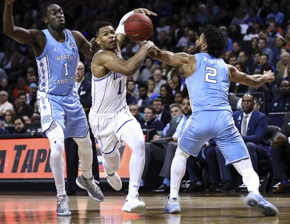 <p>Theo Pinson (1) and Joel Berry II (2) strip the ball from Duke's Trevon Duval (1) during the ACC semifinals on March 9 in Brooklyn. Photo courtesy of David Welker, theACC.com.</p>