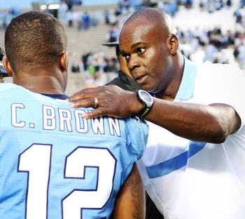 Coach Everett Withers speaks to cornerback Charles Brown during the Tar Heel's game against the University of Virginia.