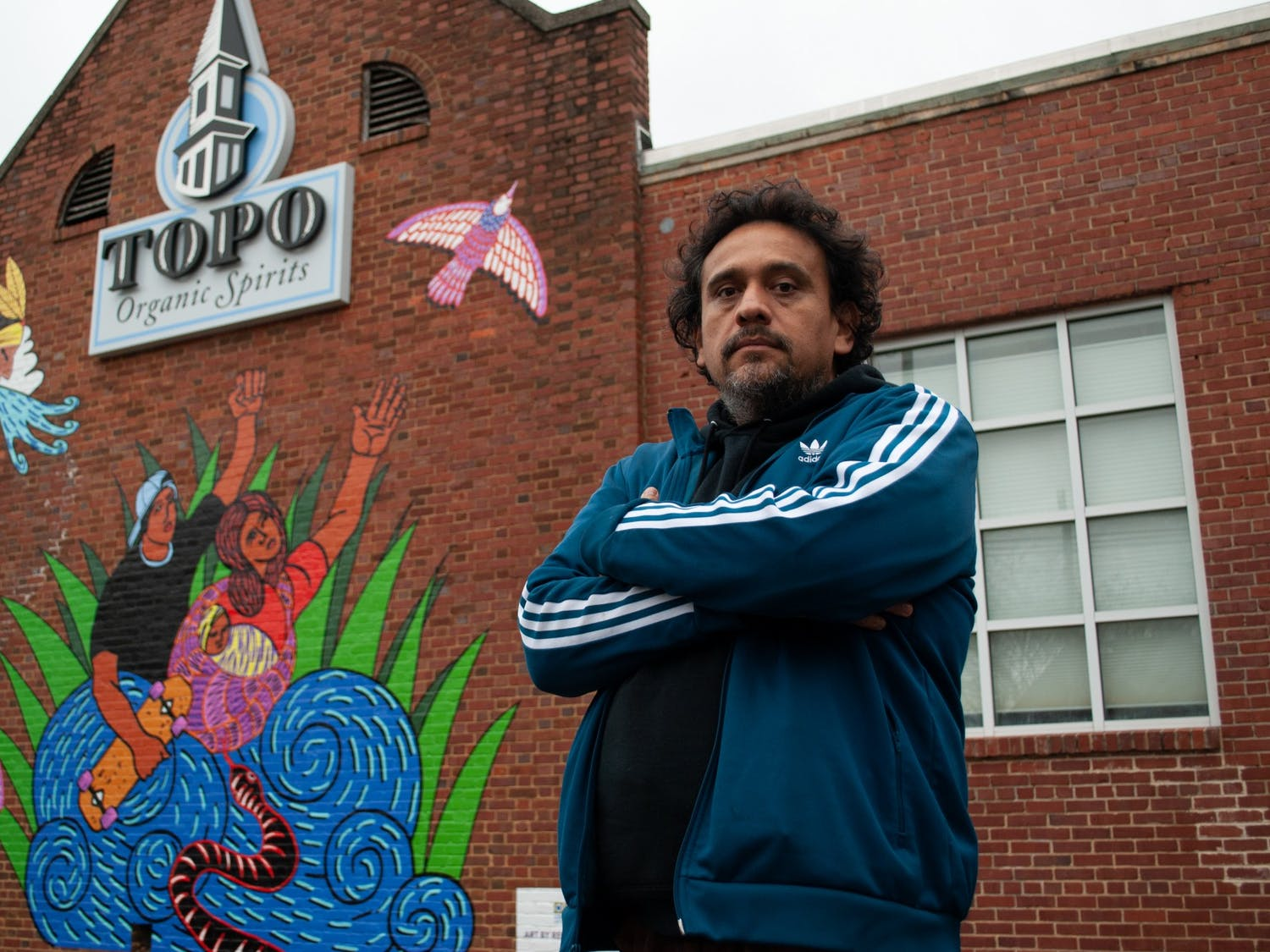 "Renzo Ortega poses for a portrait with his work ""Successions"". The new mural at TOPO Distillery pays tribute to family bond dynamics, especially those of family members that have left and have yet to return."