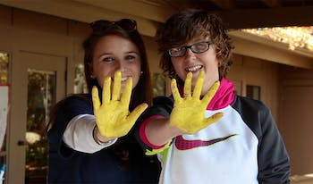 "Molly Laux and Valerie King show their painted hands after contributing their handprints to a banner that says, ""Together we are brave."""