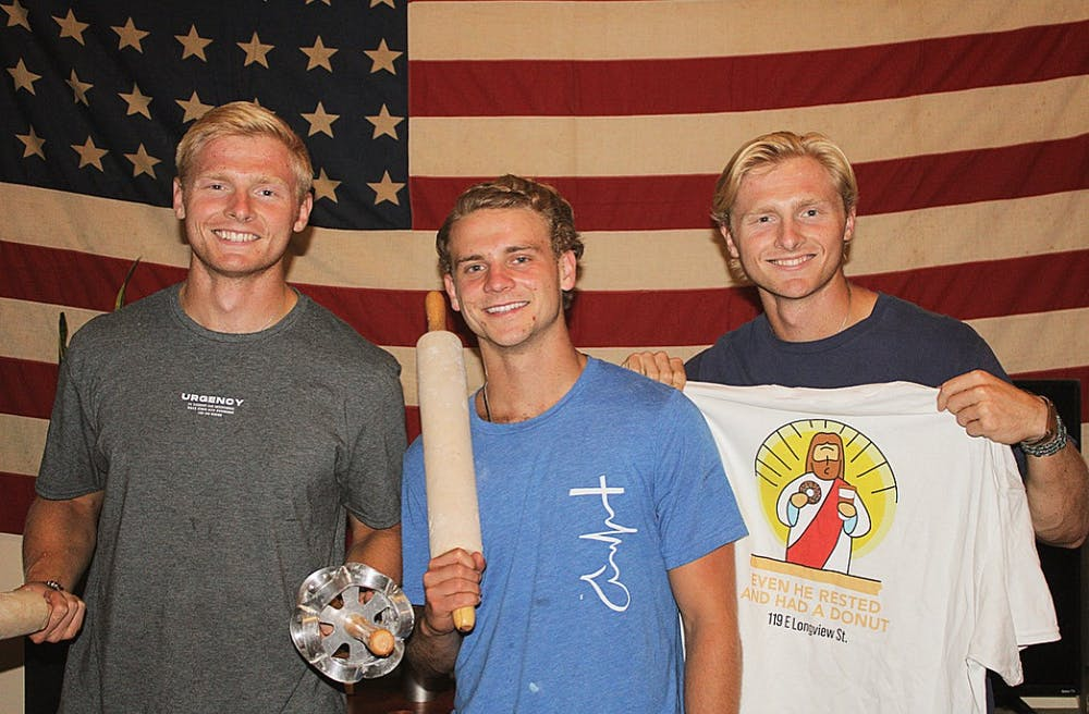Chapel Hill Housemates Harrison Schertzinger, Diego Vallota, and Henry Schertzinger, pose in front of an American Flag and show off NANDO's merchandise. Photo Courtesy of NANDO's Donuts.