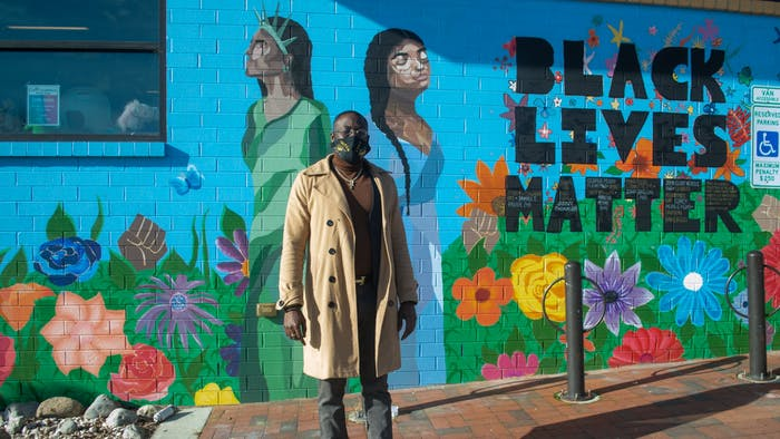 Ty Small, Coordinator of the Black Lives Matter Mural at the Community Worx building in Carrboro, stands in front of his work on Monday Jan. 11 2021.