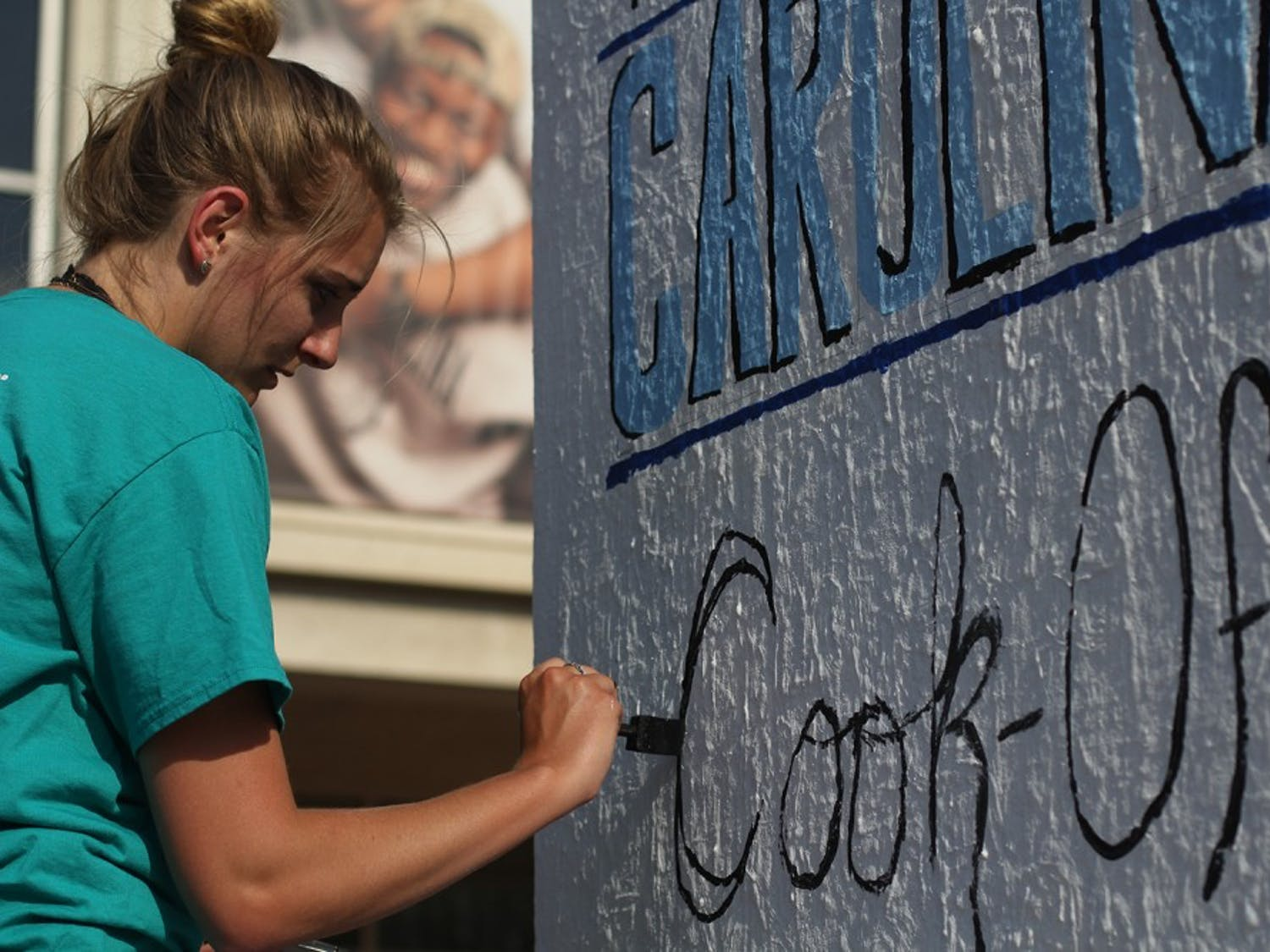 Kristen Wagner, the co-chair of the event, paints on one of the blocks in the pit in hopes of publicizing for the The Great Carolina Cook-Off.