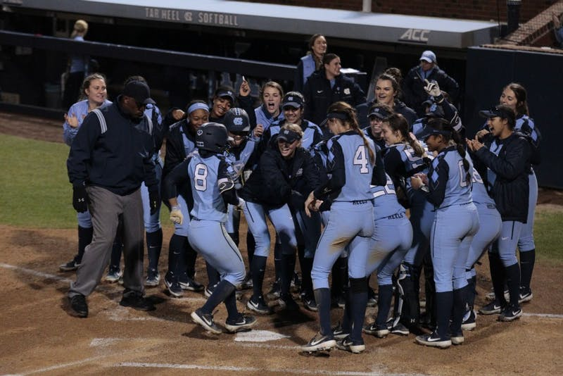 The UNC women's softball team welcomes junior outfielder Kiani Ramsey (8) to the home plate after she hit a home-run during UNC's 11-5 win over Maryland at Anderson Stadium on Sat. March 2, 2019.