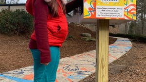 A young girl stands by an interactive mural that is part of the Make Your Mark series of sidewalk murals around Raleigh. Photo courtesy of Anna Totten