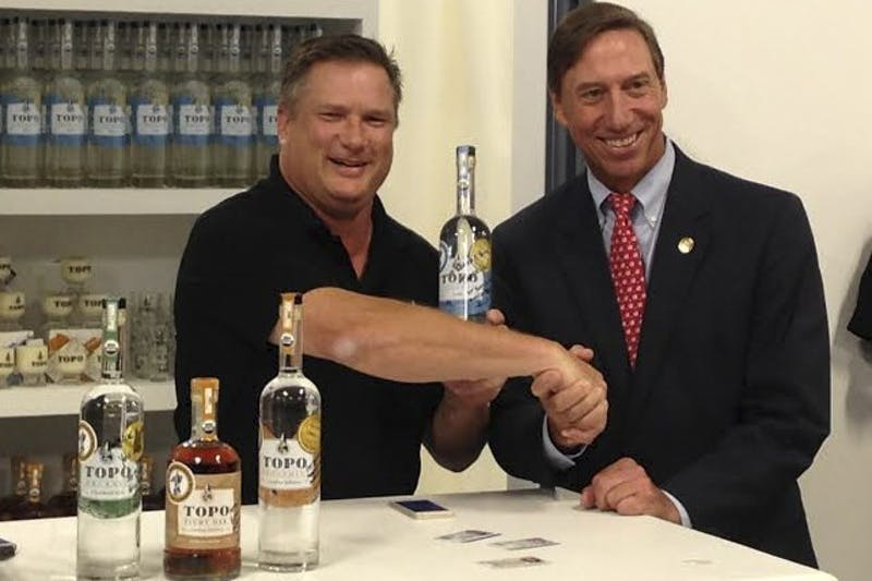 TOPO Distillery owner Scott Maitland (left) sells liquor to state Sen. Rick Gunn.