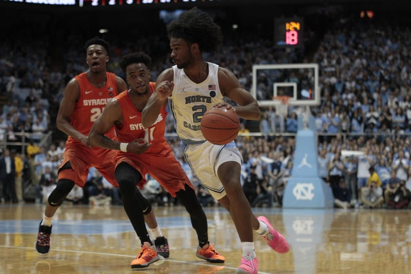 First-year guard Coby White dribbles past a Syracuse defender in the Smith Center on Tuesday, Feb. 26, 2019. White hit a new career high 34 points. UNC beat Syracuse 93-85.