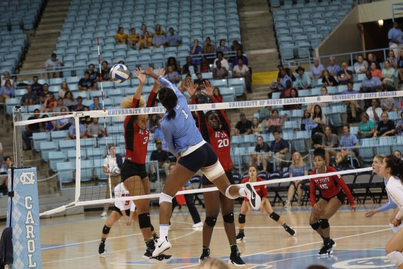 Destiny Cox, freshman and outside hitter for UNC's women's volleyball team, spikes the ball for another point in a game against N.C. State on Wednesday, Sept. 29, 2018.