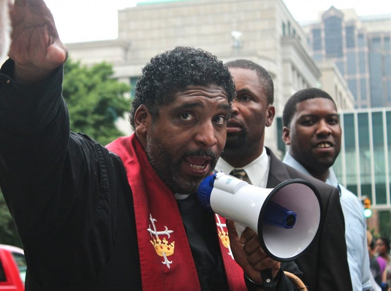 "Rev. William Barber tells people at the rally that an oncoming storm would force the ""Moral Monday"" to end early, before the 151 arrested had left the building."