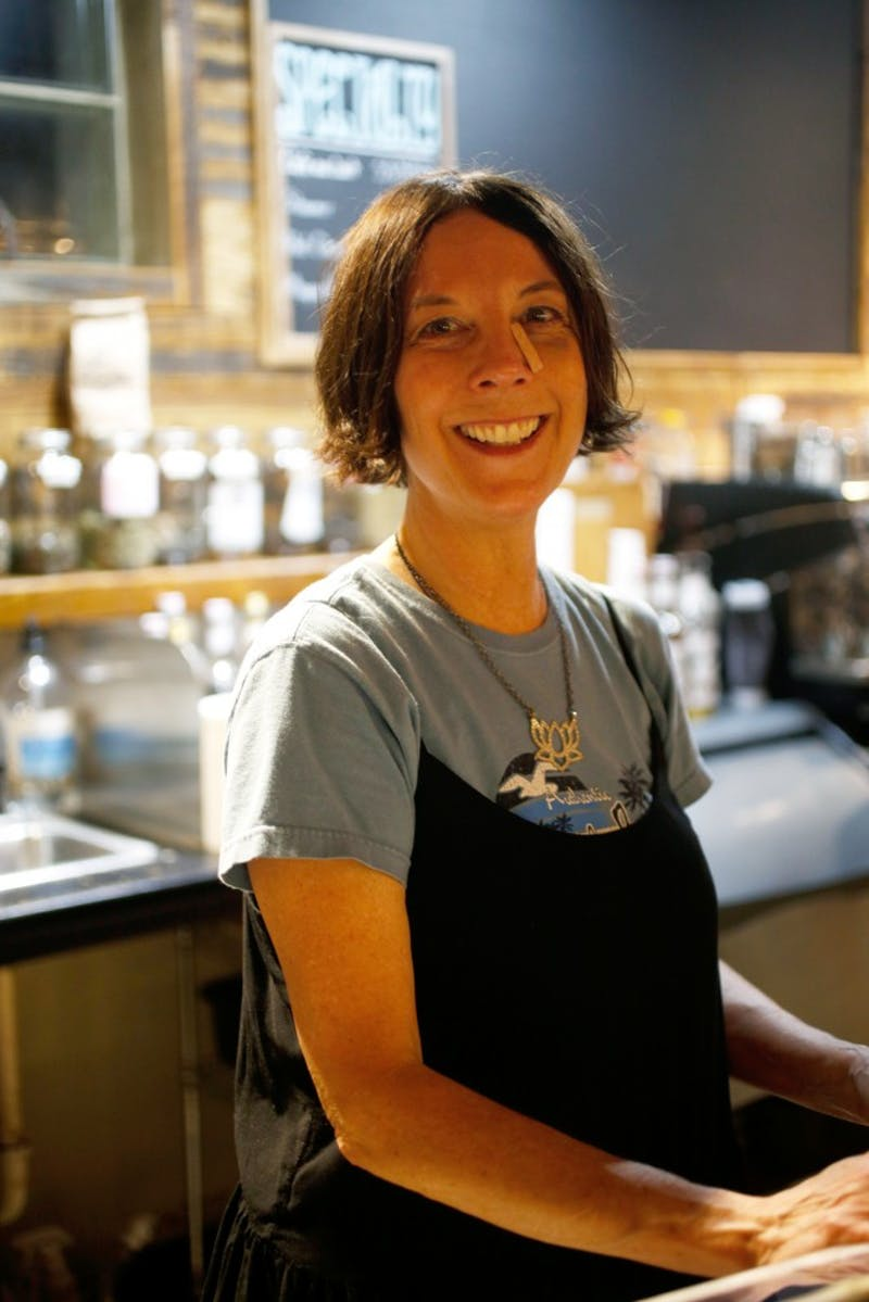 "Laura Locke works at Looking Glass Cafe, now The Honeysuckle Cafe & Bar, in Feb. 2019. Locke recently moved to the Carrboro area from Floyd, Virginia, and she works as a barista at Looking Glass Cafe in Carrboro, NC. Locke says one thing she enjoys most about Looking Glass is their commitment to connecting people to the farms and land around them. Locke is especially passionate about Looking Glass' efforts to connect customers with the land around them as well as the protection of land and water. ""If we don't have land and water, what do we have?"" Locke said. ""[Looking Glass Cafe] is hoping to bring more people in the door and inspire them to get connected to the land."""