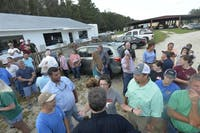 North Carolina Gov. Roy Cooper, foreground, back to camera, talks with farmers on Friday, Sept. 21, 2018, at a stop in Trenton, N.C., as he tours agricultural areas of the state hit hard by Hurricane Florence. (Scott Sharpe/Raleigh News & Observer/TNS)