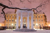 Students gather around the Old Well to enjoy the snow late Tuesday night.