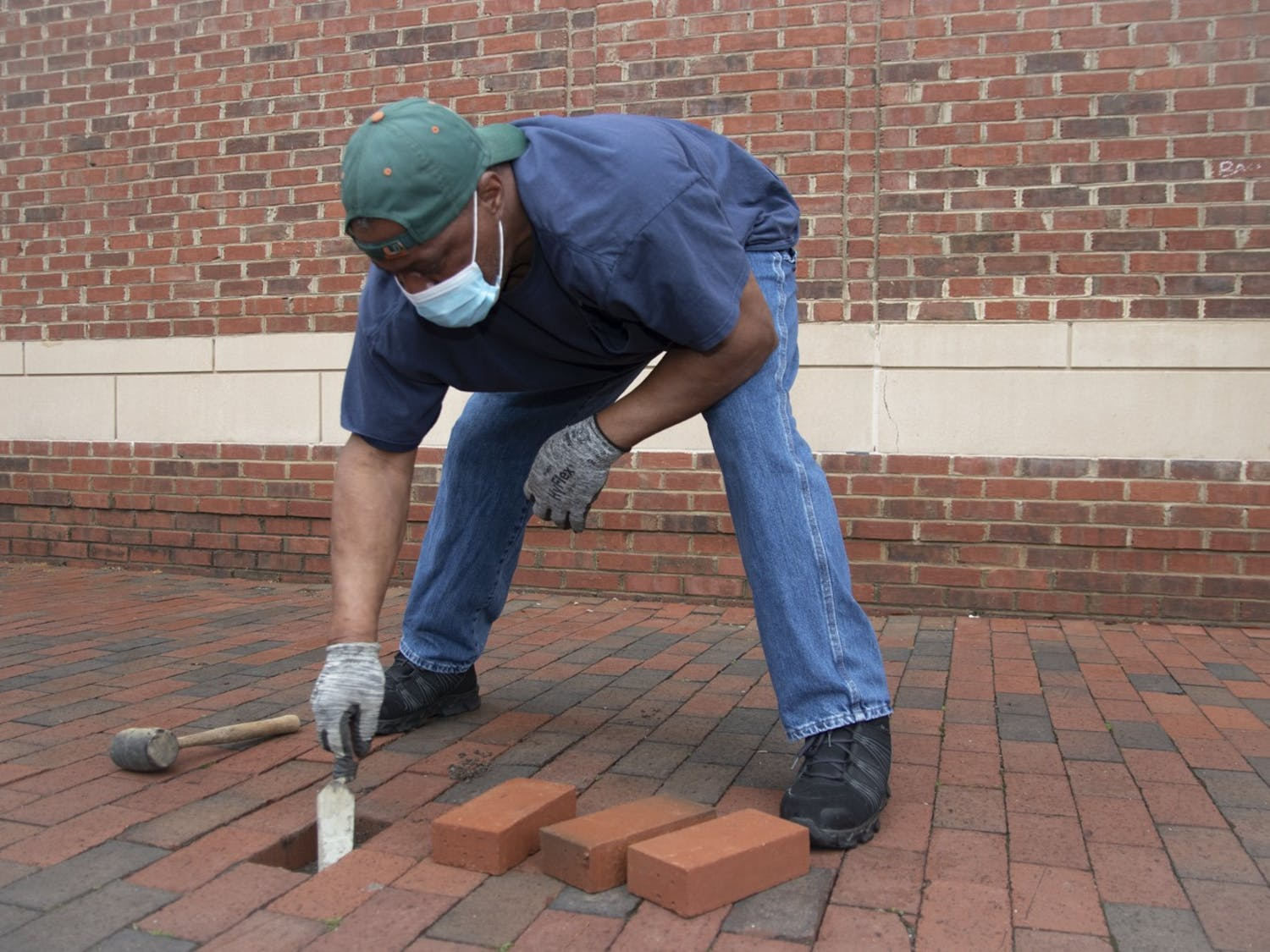 UNC faculty member Walter Thompson fills in missing bricks next to Rams Head Recreation Center on Friday, Mar. 26, 2021. Thompson spends every weekday searching for missing bricks on campus to replace them.