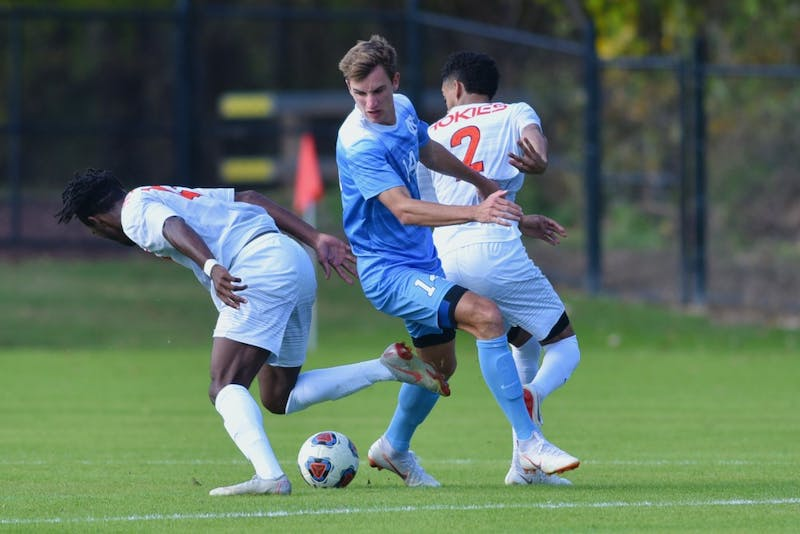 Senior forward Nils Bruening (14) fights for the ball against Virginia Tech. UNC defeated Virginia Tech 3-0 on senior day, Nov. 4 at Finley Field.
