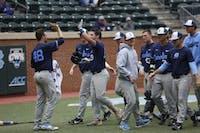 Bret Daniels high fives his teammates after hitting a home run.