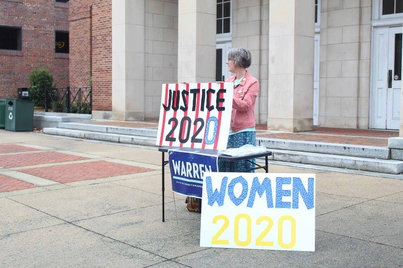 Warren supporter Tara Pressley stands in the Peace and Justice Plaza with voting signs on Tuesday, Feb. 25, 2020.