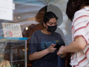 An employee of Little Waves Cafe speaks with a customer on April 9, 2021.