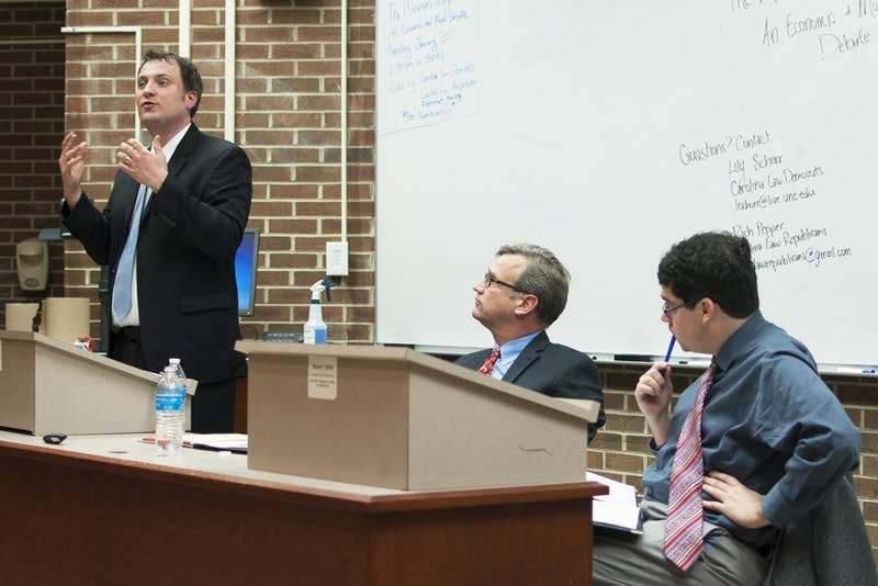 T. William Lester (left) and Adam Smith (right) debate the moral and economic impacts of possibly raising the federally mandated minimum wage at Van Hecke-Wettach Hall on Tuesday.