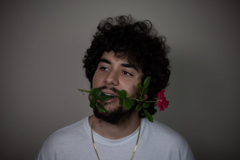 Sports Editor, PJ Morales, holds a flower in his mouth to recreate a photo of Drake.