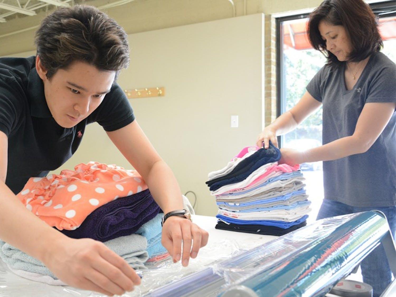 Shuya Osada works on getting folded clothes wrapped in plastic wrap while Yoshia Osada lends a hand.