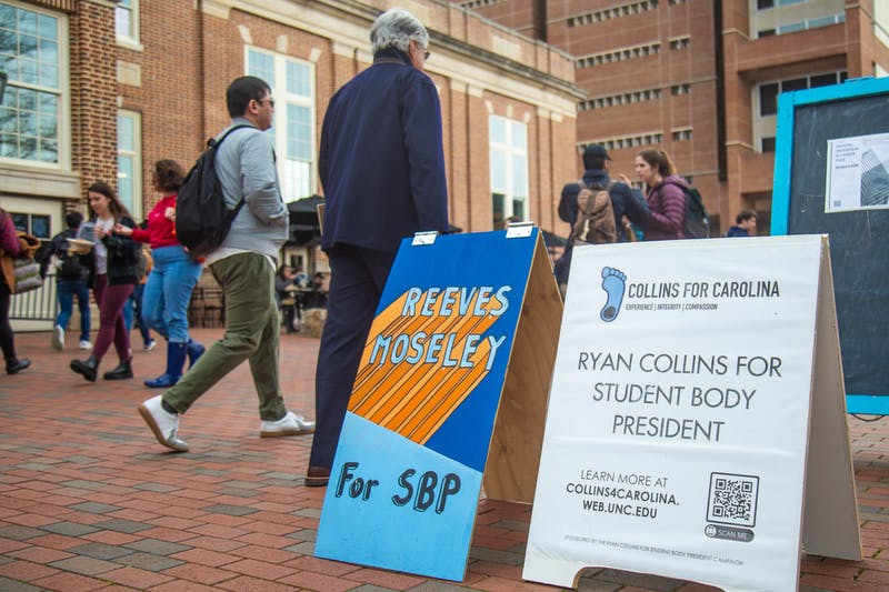 UNC faculty and students walk past ad campaigns in the Pit ahead of the Student Body President election on Feb. 10, 2020. Voting for the Student Body President Election begins on Feb. 11 at heellife.unc.edu.