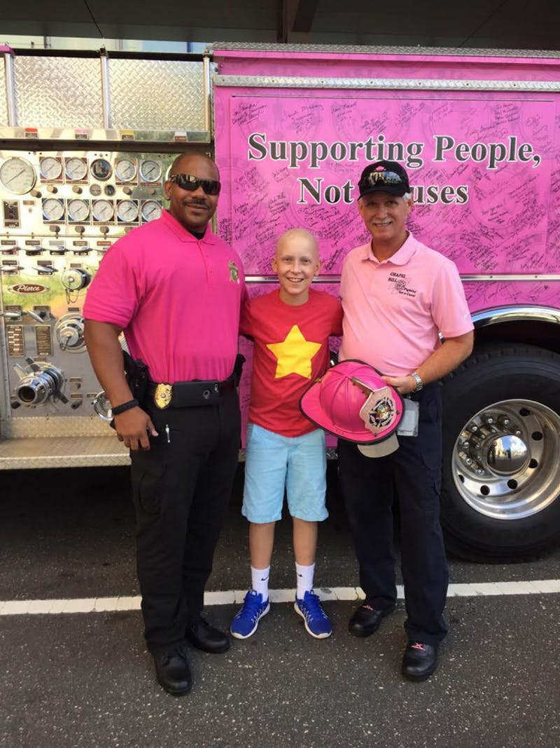 Community liaison for crime prevention Lieutenant B. Green stands with Jackson Donahoe andChapel Hill Fire Department Training Captain Byron Greeson.