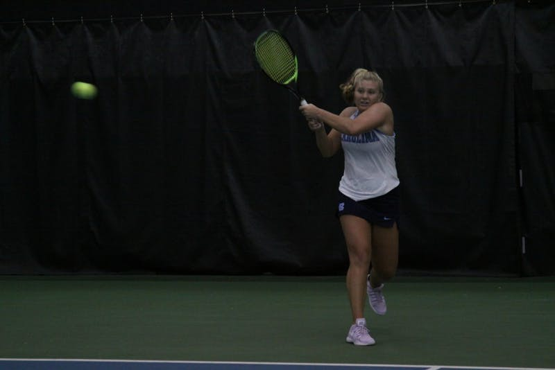 First-year Alle Sanford follows through after a backhand against Michigan on Feb. 18 in the Cone-Kenfield Tennis Center.