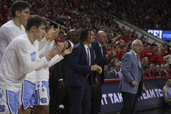 The UNC men's basketball team celebrates after one of their teammates scores a basket during the game against N.C. State in PNC Arena on Monday, Jan. 27, 2020. UNC beat State 75-65.
