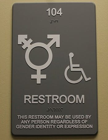 A gender non-specific bathroom sign hangs outside a Campus Y bathroom.