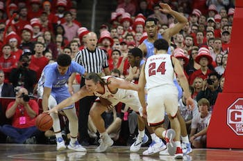 UNC and NC State players scramble for the ball in PNC Arena Tuesday, Jan. 8, 2019. UNC defeated NC State 90-82.