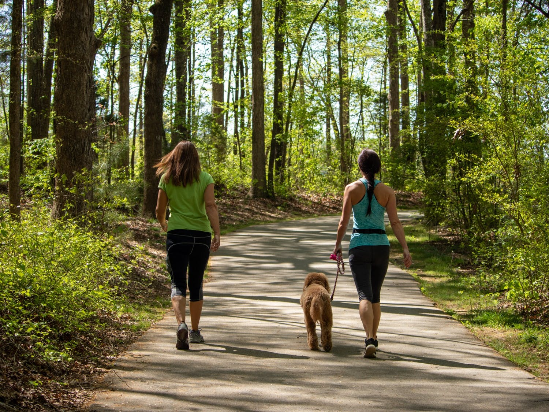 Two women walk their dog in Cornelius, NC on Monday, Apr. 12, 2021.