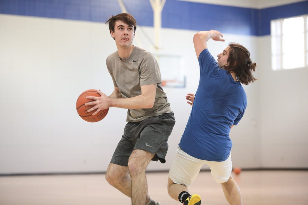 Ryan Wilcox (left) sports editor of The Daily Tar Heel, swivels past a staffer at Duke's Chronicle during a scrimmage in Brodie Recreation Center on Duke's campus on Sunday, Jan. 26, 2020. The Daily Tar Heel beat the Chronicle three games to one.