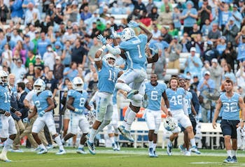Safety Myles Dorn (1) celebrates with teammates after recording his first career interception against Notre Dame on Oct. 7 in Kenan Memorial Stadium.